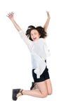 Mujer alegre joven en un salto Fotos de archivo