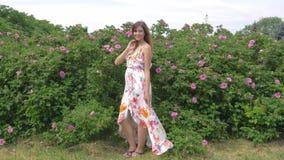 Retrato de una mujer bastante alegre en un vestido en Rose Bush almacen de video