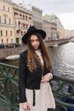 Retrato de una mujer bastante de moda de los jóvenes que presenta mientras que se coloca en un puente del río en un día de primav Foto de archivo