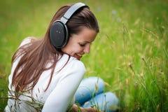 Retrato de una mujer bastante joven que escucha la música Imagenes de archivo