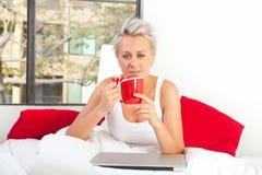 Retrato de una mujer bonita que se sienta en su cama con un ordenador portátil y Foto de archivo libre de regalías