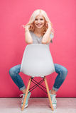 Retrato de una mujer bonita sonriente que se sienta en la silla Fotos de archivo libres de regalías