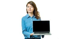 Retrato de una mujer casual feliz que muestra el ordenador portátil en blanco s Foto de archivo libre de regalías