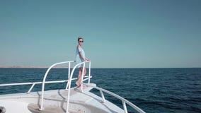 Retrato de una mujer caucásica atractiva hermosa joven en un yate adentro en un vestido azul y gafas de sol El concepto de vacaci almacen de video