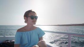 Retrato de una mujer caucásica atractiva hermosa joven en un yate adentro en un vestido azul y gafas de sol El concepto de vacaci metrajes