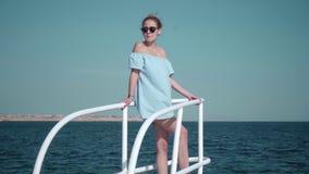 Retrato de una mujer caucásica atractiva hermosa joven en un yate adentro en un vestido azul y gafas de sol El concepto de vacaci almacen de metraje de vídeo