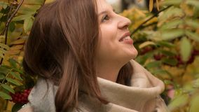 Retrato de una mujer caucásica atractiva que sonríe contra un fondo del follaje del otoño Imagen de archivo