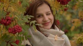 Retrato de una mujer caucásica atractiva que sonríe contra un fondo del follaje del otoño Fotos de archivo libres de regalías