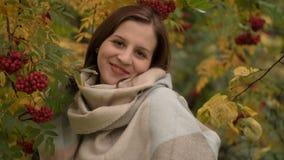 Retrato de una mujer caucásica atractiva que sonríe contra un fondo del follaje del otoño Imagen de archivo libre de regalías