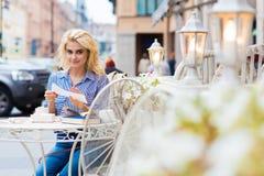 Retrato de una mujer caucásica rubia asombrosa que presenta mientras que se sienta con los libros en cafetería en el aire fresco, Fotografía de archivo