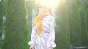 Retrato de una mujer ciega hermosa joven en un hijab con un bastón afuera en un día soleado almacen de video