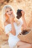 Retrato de una mujer con la uva en manos Foto de archivo libre de regalías