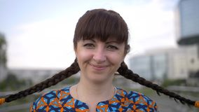Retrato de una mujer con las trenzas en su cabeza, mirando la cámara y la sonrisa fotos de archivo