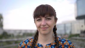 Retrato de una mujer con las trenzas en su cabeza, mirando la cámara y la sonrisa foto de archivo libre de regalías