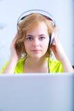Retrato de una mujer con los auriculares delante de un cálculo del ordenador portátil Imagen de archivo libre de regalías