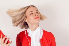 Retrato de una mujer con los auriculares y el teléfono móvil a disposición en chaqueta roja en el fondo blanco Foto de archivo libre de regalías