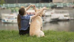 Retrato de una mujer con su perro hermoso que miente al aire libre fotos de archivo