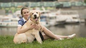 Retrato de una mujer con su perro hermoso que miente al aire libre foto de archivo