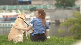 Retrato de una mujer con su perro hermoso que miente al aire libre metrajes