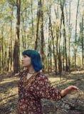 Retrato de una mujer con un aspecto interesante que camina en el bosque foto de archivo