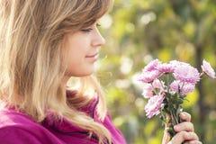Retrato de una mujer con un ramo de flores de crisantemos Fotos de archivo libres de regalías