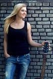 Retrato de una mujer con una guitarra cerca de la pared de ladrillo Imagen de archivo