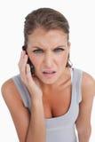 Retrato de una mujer confusa que hace una llamada de teléfono Imagenes de archivo