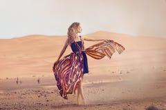 Retrato de una mujer de la belleza en un vestido en el desierto caliente fotos de archivo