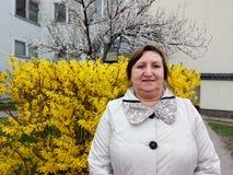 Retrato de una mujer de mediana edad en el fondo de un arbusto amarillo Fotos de archivo