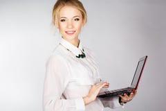 Retrato de una mujer de negocios feliz joven con un ordenador portátil Foto de archivo libre de regalías