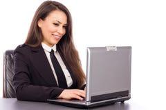 Retrato de una mujer de negocios joven feliz que usa el ordenador portátil Foto de archivo