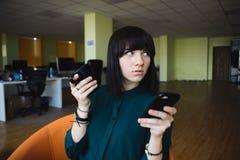 Retrato de una mujer de negocios joven, hermosa que utiliza un teléfono móvil y un café de consumición Trabajo de la rotura Ofici Imágenes de archivo libres de regalías