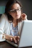 Retrato de una mujer de negocios maduros pensativa que mecanografía en el ordenador portátil Fotos de archivo libres de regalías