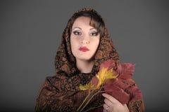 Retrato de una mujer de pelo oscuro hermosa con una bufanda en su cabeza y hojas de otoño Fotos de archivo
