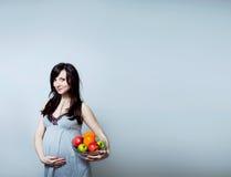 Retrato de una mujer embarazada con la fruta colorida Fotografía de archivo libre de regalías