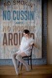 c691a99ce Retrato de una mujer embarazada joven en la camisa blanca en estudio de la foto  foto