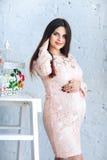 Retrato de una mujer embarazada joven en un vestido rosado contra una pared blanca que mira la cámara Foto de archivo libre de regalías