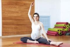 Retrato de una mujer embarazada joven hermosa que hace ejercicios Elaboración, yoga y aptitud, concepto del embarazo imagen de archivo