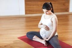 Retrato de una mujer embarazada joven hermosa que sienta en la yoga Mat On un fondo de madera Foto de archivo libre de regalías