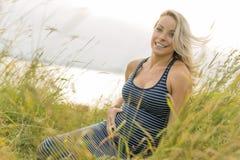 Retrato de una mujer embarazada rubia hermosa joven en el lado de la playa Imagen de archivo libre de regalías