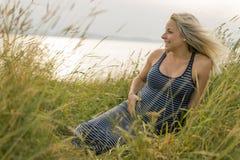Retrato de una mujer embarazada rubia hermosa joven en el lado de la playa Imagenes de archivo
