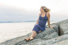 Retrato de una mujer embarazada rubia hermosa joven en el lado de la playa Imagen de archivo