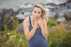 Retrato de una mujer embarazada rubia hermosa joven en el lado de la playa Fotos de archivo libres de regalías
