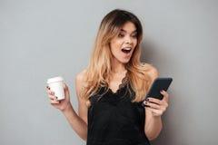 Retrato de una mujer emocionada joven que mira el teléfono móvil Foto de archivo libre de regalías