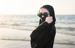 Retrato de una mujer en abaya en la playa Imagen de archivo libre de regalías