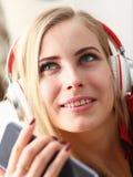 Retrato de una mujer en casa en auriculares Fotografía de archivo libre de regalías