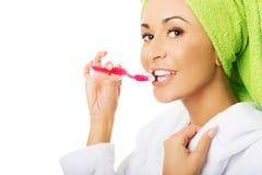Retrato de una mujer en dientes de cepillado de la albornoz Fotos de archivo