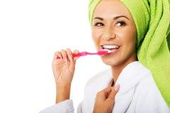 Retrato de una mujer en dientes de cepillado de la albornoz Imagen de archivo