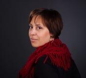 Retrato de una mujer en la bufanda roja que mira detrás. Retrato del primer Fotos de archivo