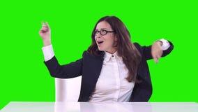 Retrato de una mujer en la oficina en un fondo verde Sonrisas morenas y danzas almacen de metraje de vídeo